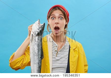 Headshot Of Emotional Surprised Young Fisherwoman Wearing Yellow Raincoat And Hat Holding Big Fish I