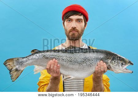 Horizontal Portrait Of Successful Angler With Beard Holding Huge Fish Which He Catched. Young Fisher