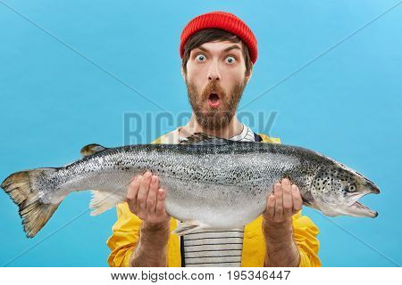 Indoor Shot Of Astonished Bearded Fisherman Dressed Casually Holding Huge Fish Looking At Camera Wit