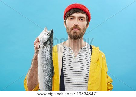 Waist Up Portrait Of Attractive Young Bearded Angler Showing Off His Catch After Recreational Fishin