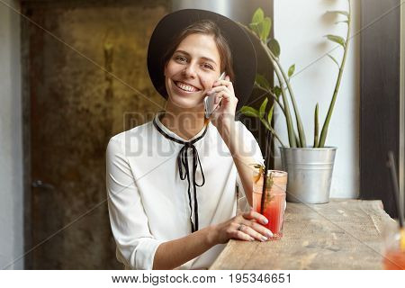 Beautiful Businesswoman Dressed In White Blouse And Black Hat Sitting At Cafe Near Window Sill Commu