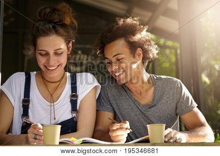 Glad European Woman Wearing Jean Overalls Sitting Near Her Afro American Friend Who Is Looking In He