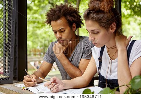 Sideways Portrait Of Black Male Student And His Girlfriend With Serious Expressions Reading Importan