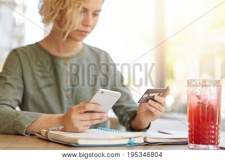 Attractive Woman With Blonde Curly Hair Wearing Elegant Blouse Sitting At Restaurant Holding Mobile