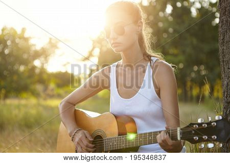 Pretty Girl Wearing White Shirt, Sunglasses Sitting At Green Grass With Guitar Learning How To Play