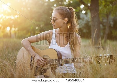 Hipster Female Teenager Enjoying Quiet Atmosphere On Nature Sitting With Guitar Singing Songs. Teena
