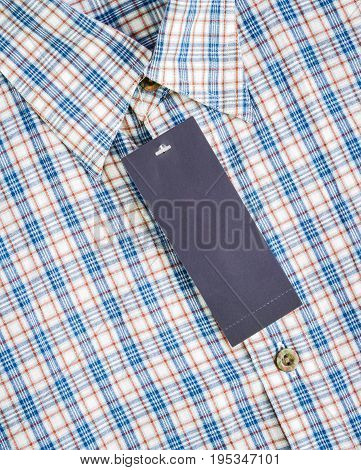 label paper tag price on blue and white checked pattern of shirt