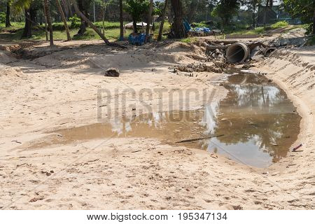 PHUKET THAILAND - 19 APR 2017: Sand Surin beach pollution from dirty drainage sewer pipe