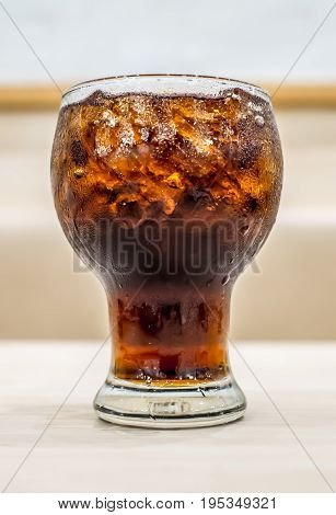 ice cola in big glass cup on wood table