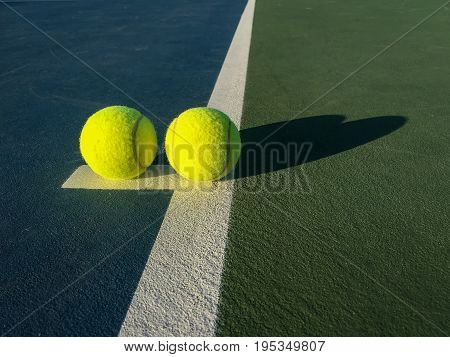 Two Bright Yellow Tennis Balls on the Tennis Court with Green and Blue Colours