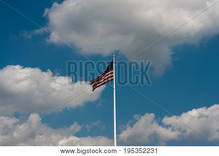 American flag flying on flag pole with blue sky and clouds