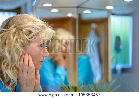 Middle-aged Woman Looking At Herself In A Mirror