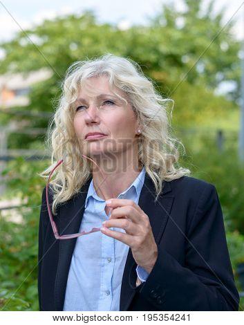 Senior Businesswoman Standing Thinking Deeply