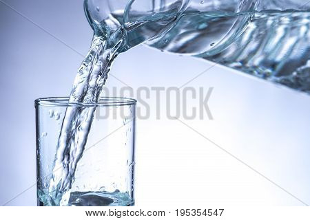 Pouring water from pitcher into a glass.