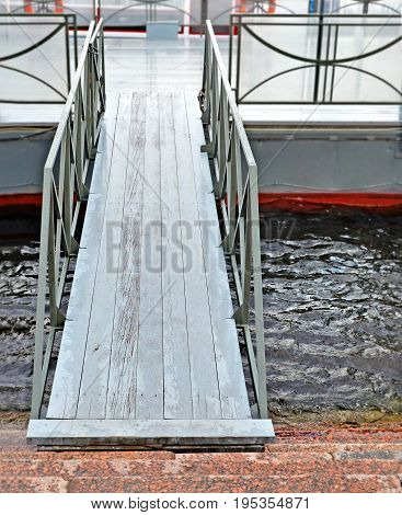 Wooden gangway between embankment and floating mooring. Background.