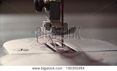 Extreme close up of needle and thread of the sewing machine