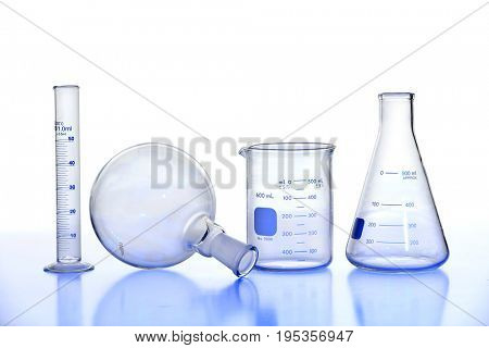 Laboratory glassware on reflective  table isolated over white background