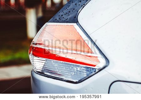 Modern blue car tail light in wet rain drop. Red modern car back light
