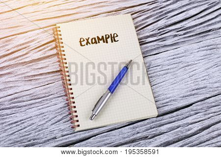 Word example on a notepad wooden background