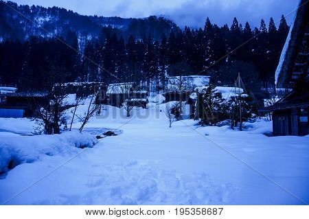 Snow Covered Ground In Winter Season. Silhouette Of Village And Trees At Night