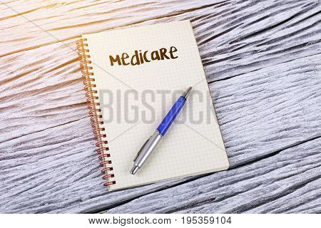 Word medicare on a notepad with wooden background