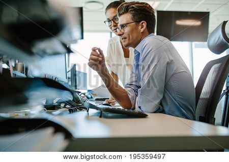 Side view of a mature businessman and businesswoman working together on desktop computer. Two business professionals looking at computer monitor.