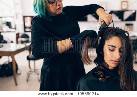 Woman getting a hairdo at salon. Hair stylist turning straight hair into curly using a hair curling iron.