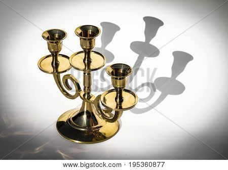 Golden candlestick on a white background with shadows close-up.