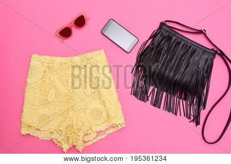 Yellow Lace Shorts, Black Bag With Fringe, Smartphone And Rose-colored Glasses. Bright Pink Backgrou