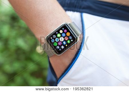 Man hand and smart touch watch with home screen icons apps in pocket