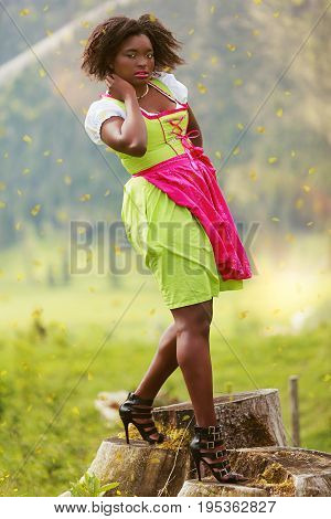 African American Young Plus Size Woman in Dirndl, standing in the open nature