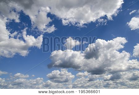 Heavy clouds in the deep blue summer sky natural wallpaper background flying high in the sky