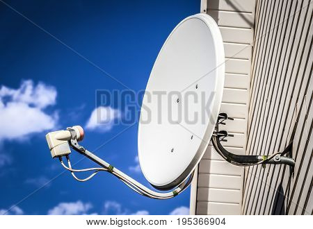 Satellite dish mounted on the wall of a private house.
