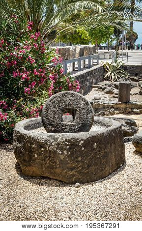 Archaeological site Capernaum on the shore of the Sea of Galilee in Israel ancient millstone for olive oil press