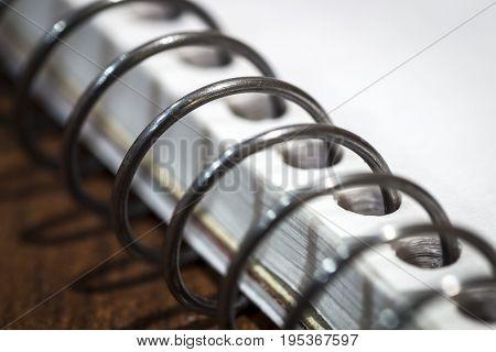 Metal chrome iron binding office notebook closeup.