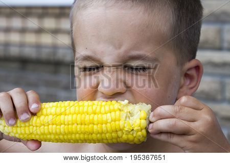 photo shoot of a child eating a corn cob Against the gray sky