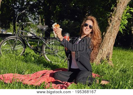 People and lifestyle concept. Joyful happy fashionable young Caucasian woman in formal suit having picnic in park with friends holding croissant and coffee inviting college to join her in lunch time.