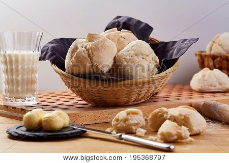Wheat bread buns in basket. Fresh tasty buns and glass of milk on wooden table.