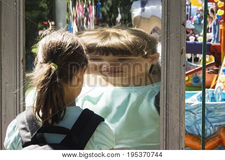 the girl looks at herself in the mirror sees himself reflected in another form.