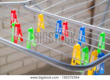 Multi-colored: red, yellow, green, blue clothespins on the clothes dryer.