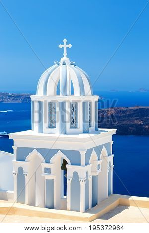 beautiful striped dome of the bell tower of the Church with the magical views of the Caldera Santorini Greece