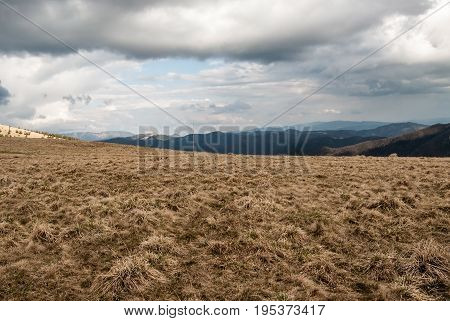 spring mountain meadow with hills on the background and blue sky with clouds in Velka Fatra mountains in Slovakia