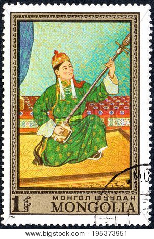 UKRAINE - CIRCA 2017: A postage stamp printed in Mongolia shows Young musician girl playing on a stringed musical instrument series Paintings by contemporary artists in Ulan Bator Museum circa 1972