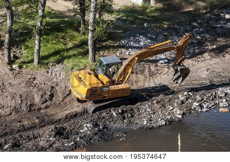 ,Backhoe working in the River Bernesga in La Pola de Gordon Leon Province Spain on July 14 2014.