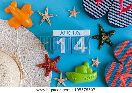 August 14th. Image of August 14 calendar with summer beach accessories and traveler outfit on background. Summer day, Vacation concept.
