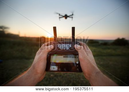 Point of view shot of man holding remote controller with his hands and taking aerial photo video. Copter is flying on background. POV - drone hovers in front of the pilot on suset. No face