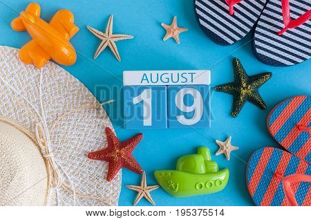 August 19th. Image of August 19 calendar with summer beach accessories and traveler outfit on background. Summer day, Vacation concept.