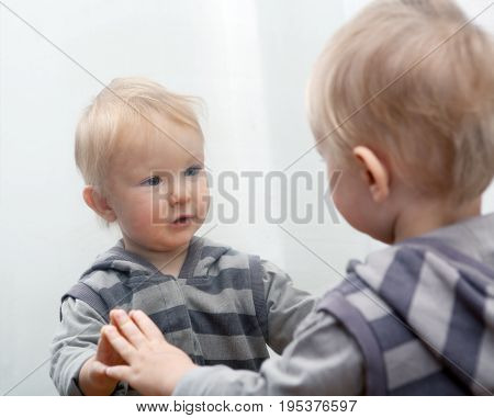 Small child looking to mirror at his face.