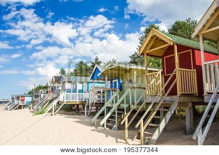 Rows of colourful, wooden beach huts that are elevated on a white, sandy beach on a beautiful summer day.