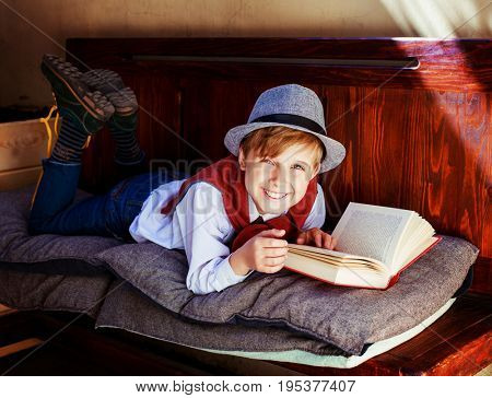 happy stylish boy with a book on the bench